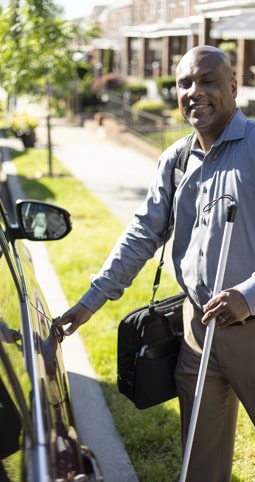 Picture of a blind person approaching his car with the help of a walking stick.